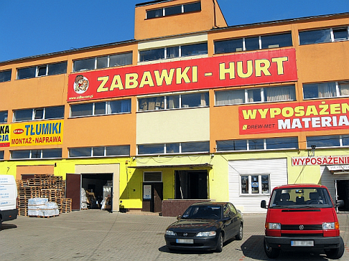 Siedziba główna naszej firmy. Pomarańczowy budynek z dużym, czerwono-żółtym napisem ZABAWKI HURT oraz logo naszej hurtowni. Przed budynkiem parking na kilkadziesiąt samochodów.